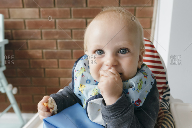 Portrait of a blonde smiling baby eating in high chair