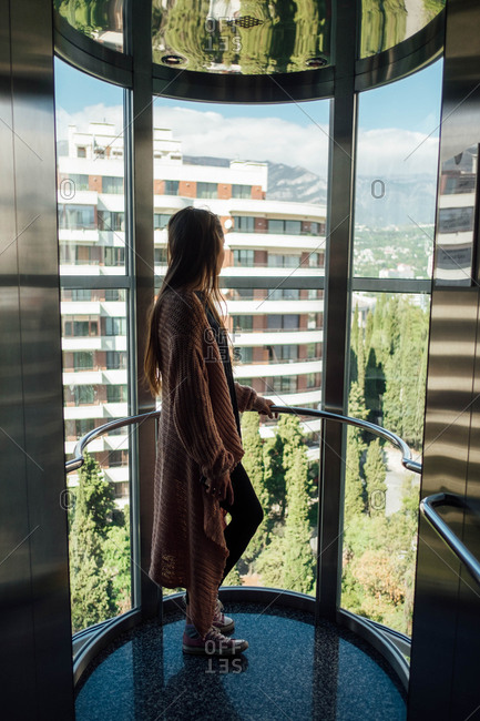 Woman rides glass elevator