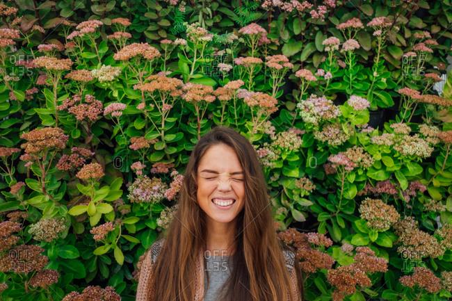 Smiling teen standing against flowering bushes