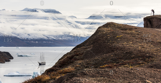Greenland - December 22, 2017: Photographer taking picture of a sailboat in the Scoresby Sound in Greenland
