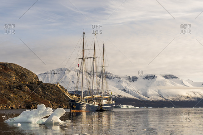 Greenland - September 6, 2017: Sailboat sailing in icy waters of Scoresby Sound in Greenland