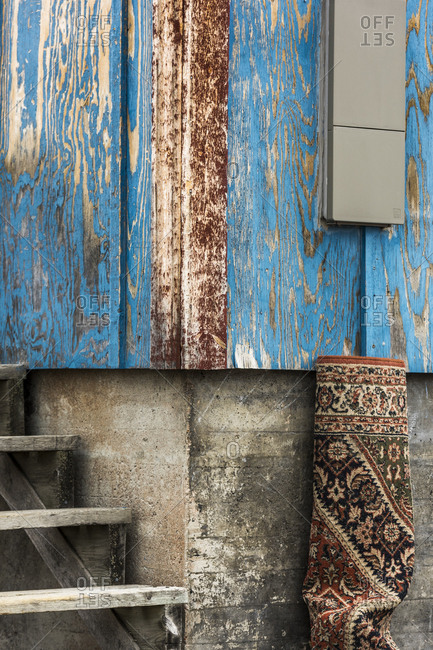 Greenland - September 11, 2017: Rolled up rug leaning on a blue cottage in a village in Greenland