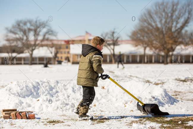Boy helping shovel snow in field