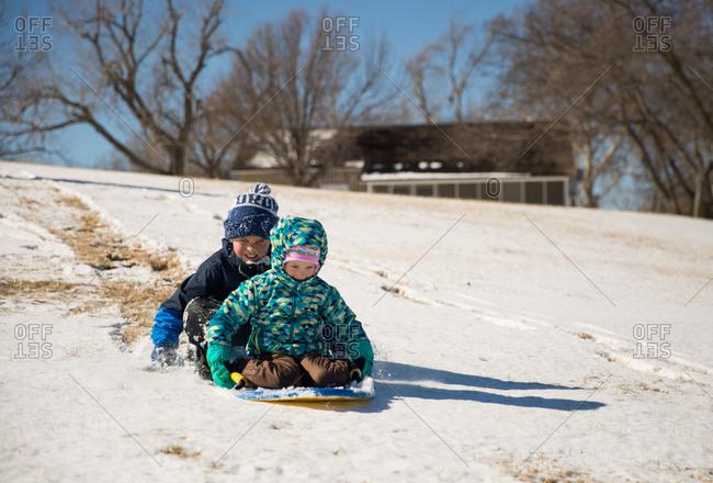 Kids sledding down hill together