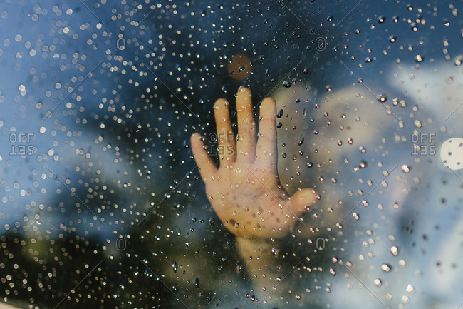 Hand grasping at wet window