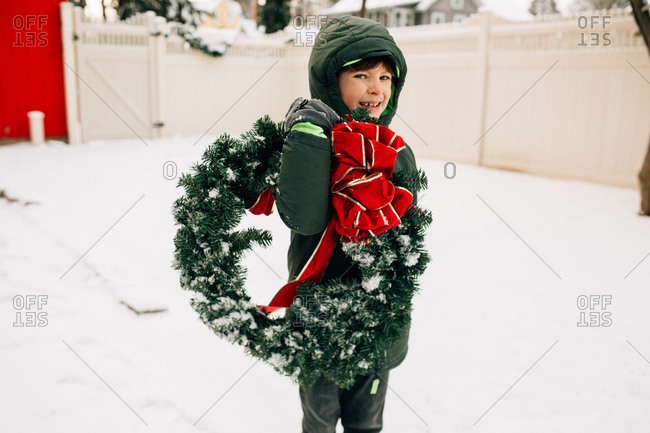 Kid carries Christmas wreath through snow