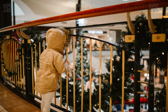 Child looks through mall balcony