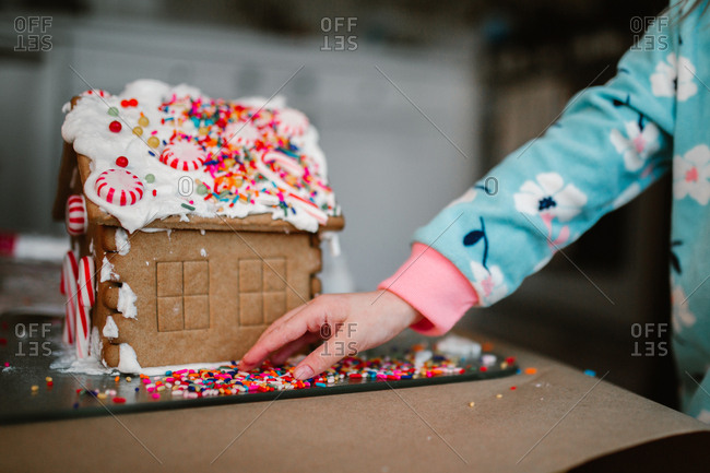 Small child arranges gingerbread house sprinkles