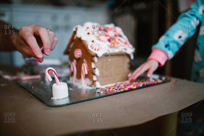Family making gingerbread house together