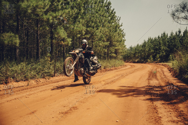 Biker doing stunts while riding motorcycle on dirt road amidst trees