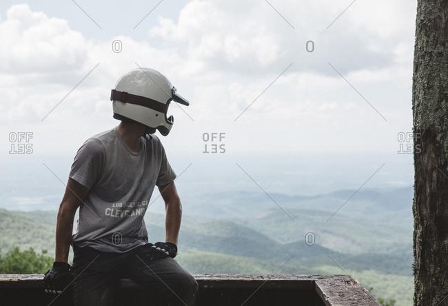 Biker wearing crash helmet while looking at view against cloudy sky