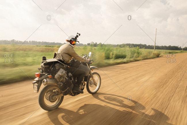 Biker wearing crash helmet while riding motorcycle on dirt road against sky