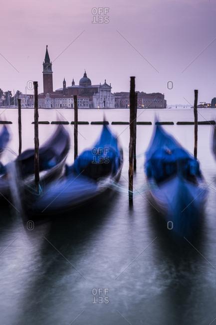 Blurred motion of gondolas moored at Venetian Lagoon against San Giorgio Maggiore at sunset