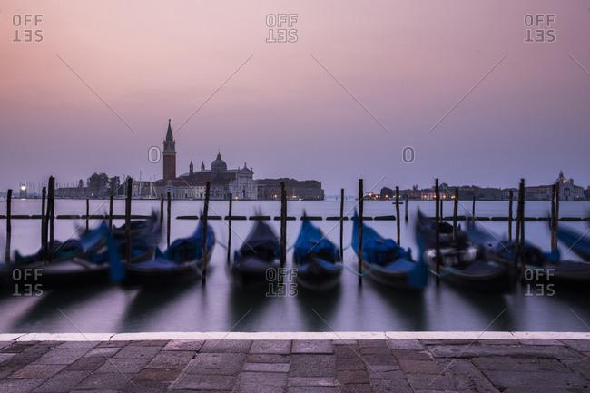 Blurred motion of gondolas moored at Venetian Lagoon against San Giorgio Maggiore during sunset