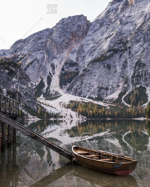 Boat moored on calm lake by mountain during winter
