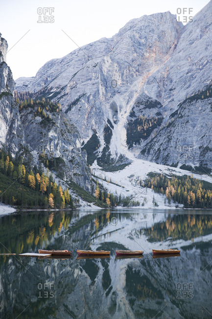 Boats moored at calm lake by mountain against sky during winter