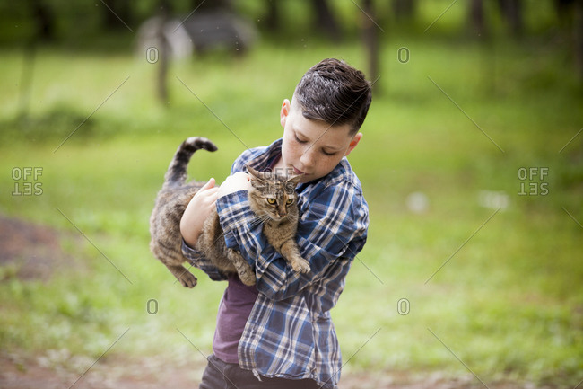 Boy holding cat while standing on field