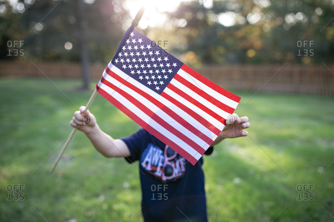 Boy showing American flag while standing on field in yard