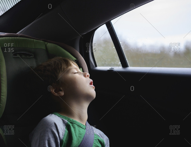 Boy sleeping while traveling in car