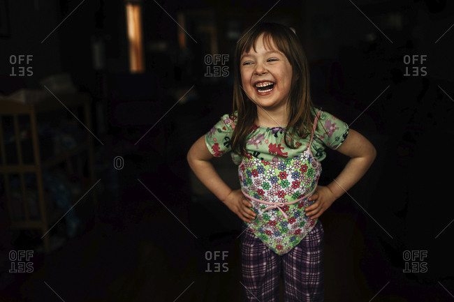 Cheerful girl with hands on hip standing in darkroom at home