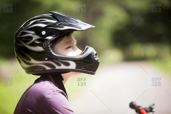 Close-up of boy wearing crash helmet while looking away