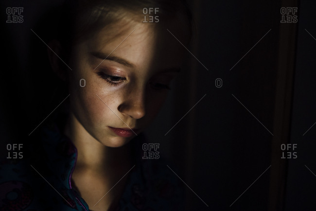 Close-up of thoughtful girl standing in darkroom at home
