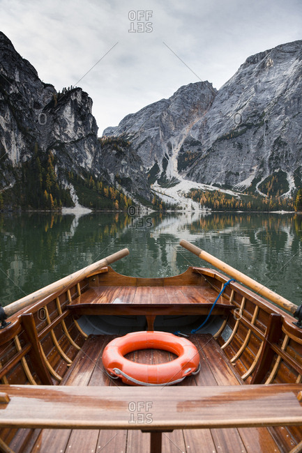 Cropped image of boat on calm lake by mountain against sky