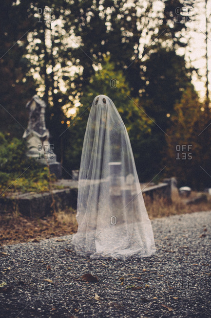Double exposure of boy in ghost costume against trees at cemetery during Halloween