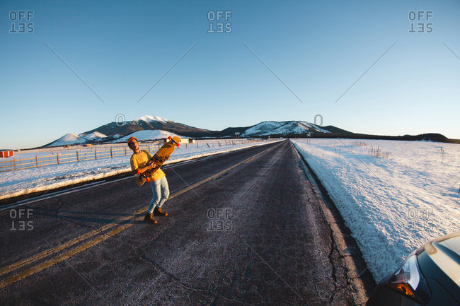 Full length of man holding skateboard while standing on road amidst snow covered field against clear blue sky