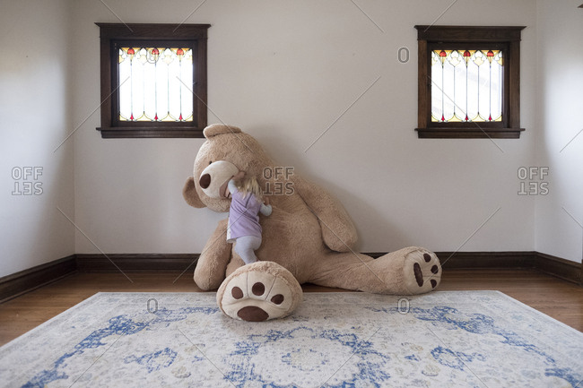 Girl playing with large teddy bear against wall at home