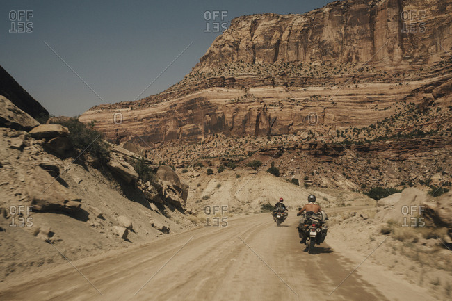 High angle view of bikers riding motorbikes on dirt road against clear sky during sunny day