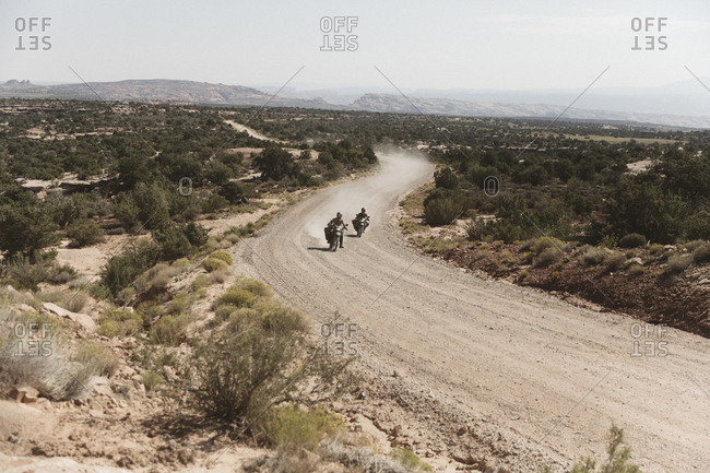 High angle view of friends riding motorbikes on dirt road against sky during sunny day