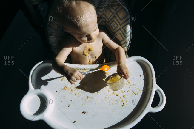 High angle view of shirtless baby boy eating food while sitting on high chair at home