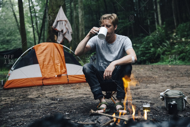 Hiker having drink at campsite in forest