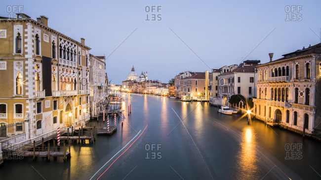 Light trails over Grand Canal amidst buildings in city during sunset