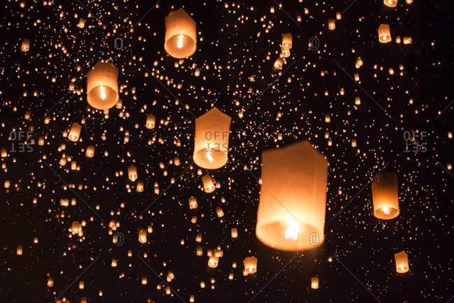 Low angle view of illuminated lanterns against sky at night