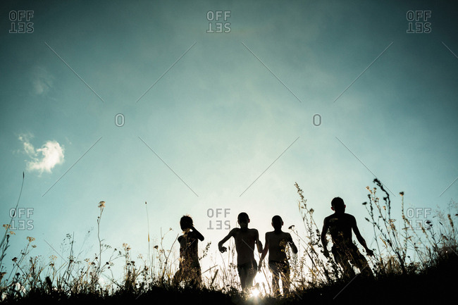 Low angle view of silhouette family jumping on field against sky during sunny day