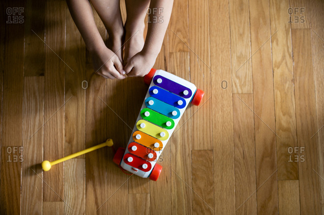 Low section of boy by xylophone on hardwood floor at home