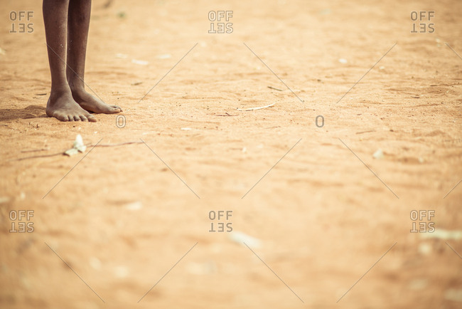 Low section of person standing on sand at desert during sunny day