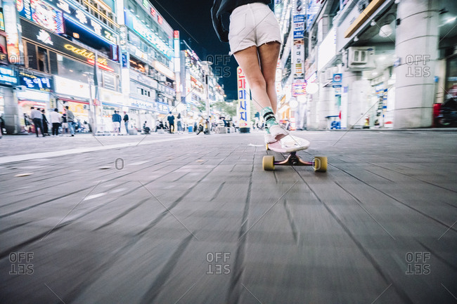 South Korea - May 20, 2017: Low section of woman skateboarding on footpath in illuminated city during night