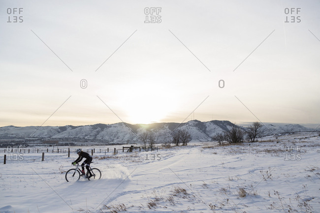 Man riding bicycle on snow covered landscape against sky during sunset