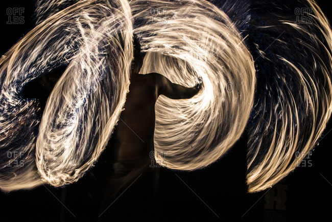 Man spinning wire wool during night