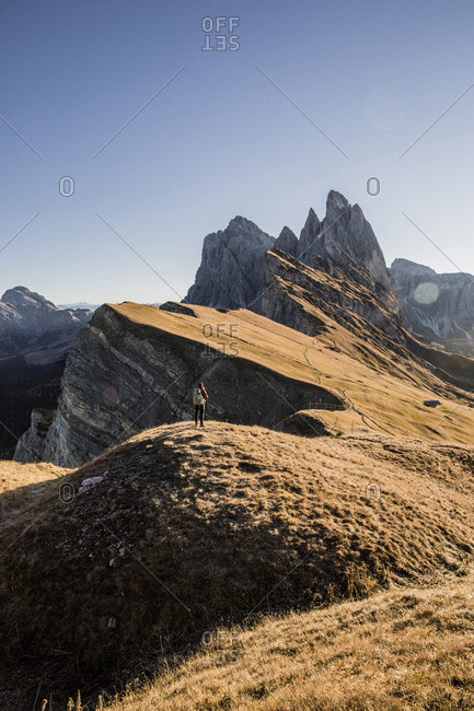 Mid distance view of hiker standing on mountain against sky during sunny day
