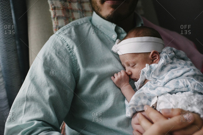 Midsection of father carrying sleeping newborn daughter while sitting on chair at home