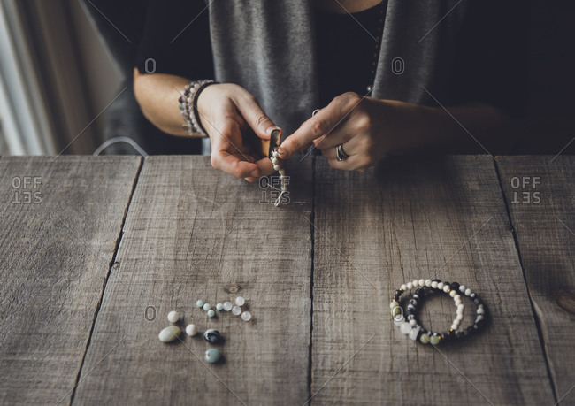 Midsection of woman making bracelets at table