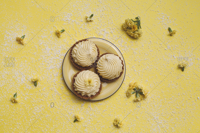 Overhead view of cupcakes in plate with flowers over yellow background