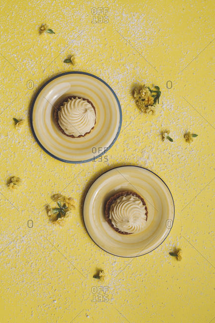 Overhead view of cupcakes in plates with flowers over yellow background