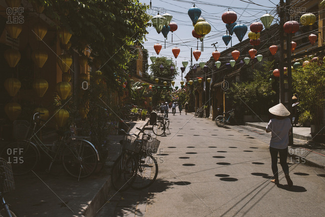 Vietnam, Hoi An - June 28, 2017: People on footpath with lantern decoration during sunny day