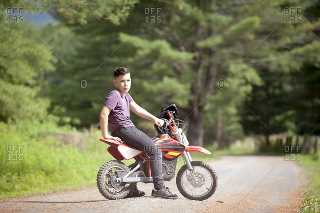 Portrait of boy sitting on dirt bike