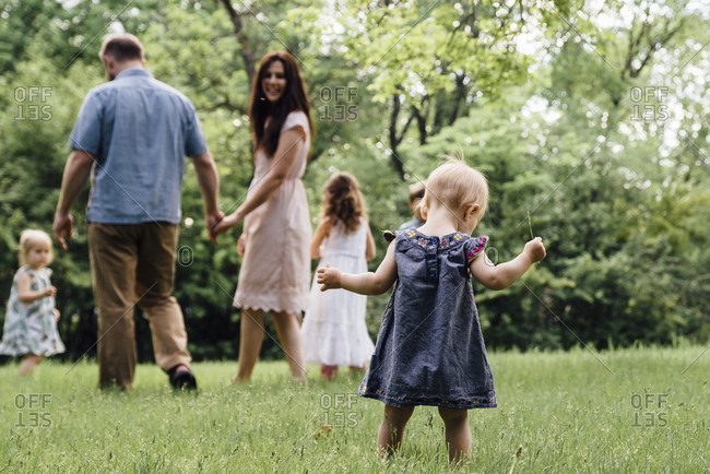 Rear view of baby girl standing against family playing on field